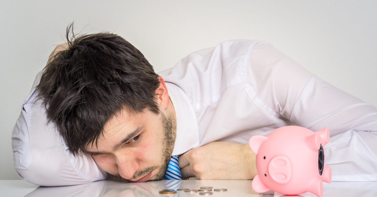Young worried man has empty piggy money bank