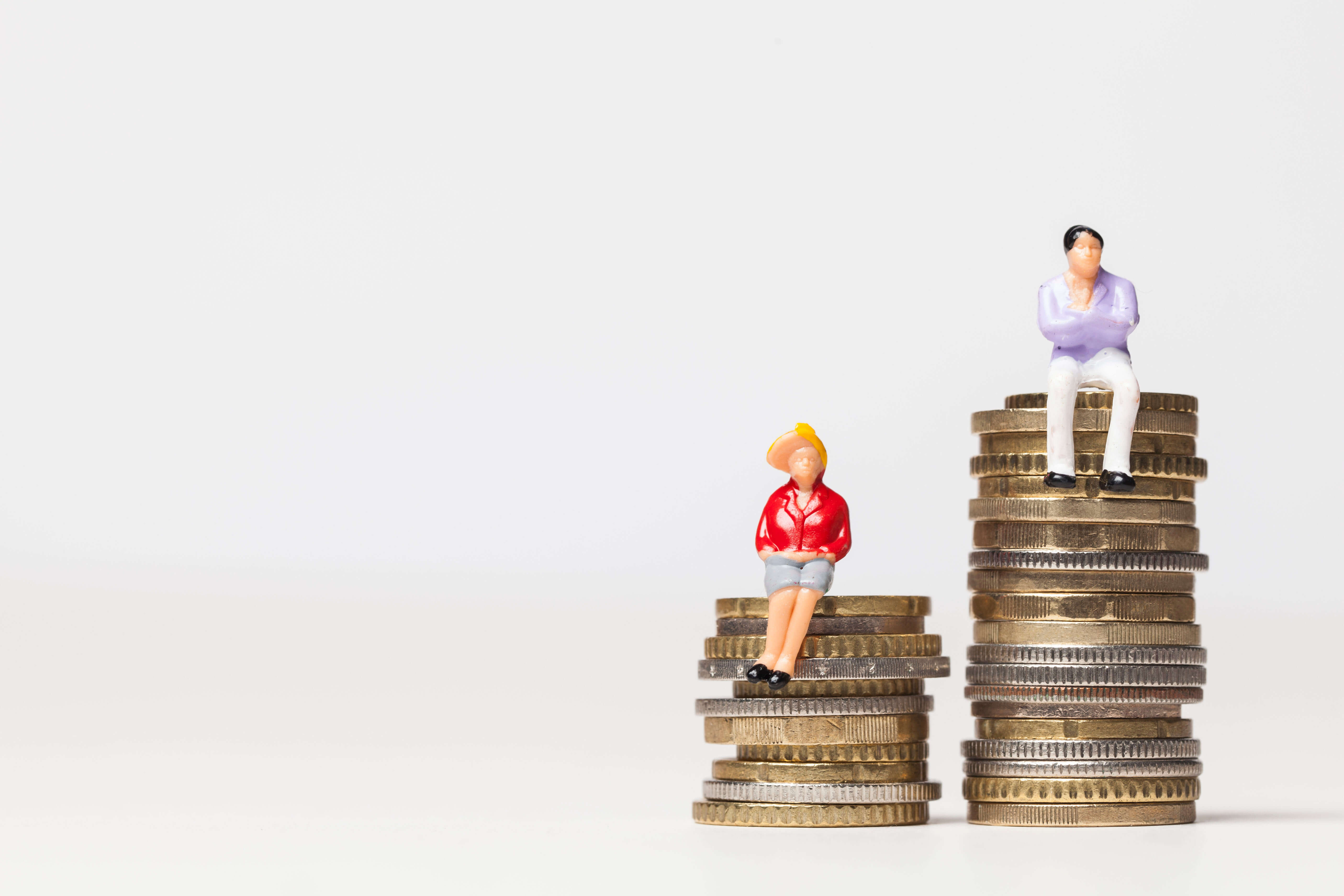 Man sitting on large tower of coins, woman on smaller tower of coins