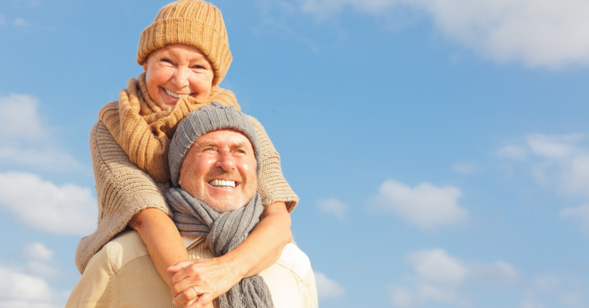 Elderly man and woman wear hats and look cosy in Winter