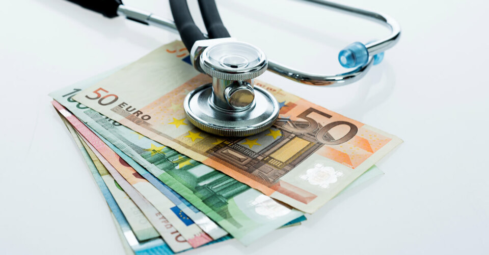 Stethoscope over a wad of euro notes