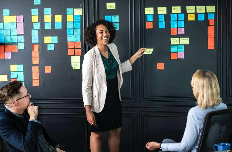 good supervisor woman laughing with two colleagues sticking post-its to the wall
