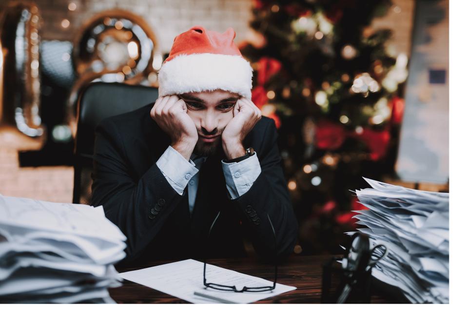 man looking grumpy at work at christmas