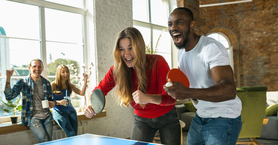 Engaged employees playing ping pong